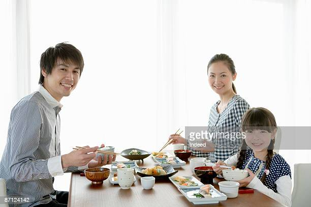 Parents and daughter eating breakfast at table