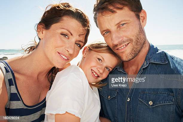 Parents and daughter (6-8) embracing, outdoors
