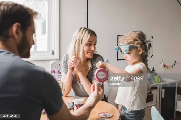 parents and daughter having tea party in playroom - tea party stock pictures, royalty-free photos & images
