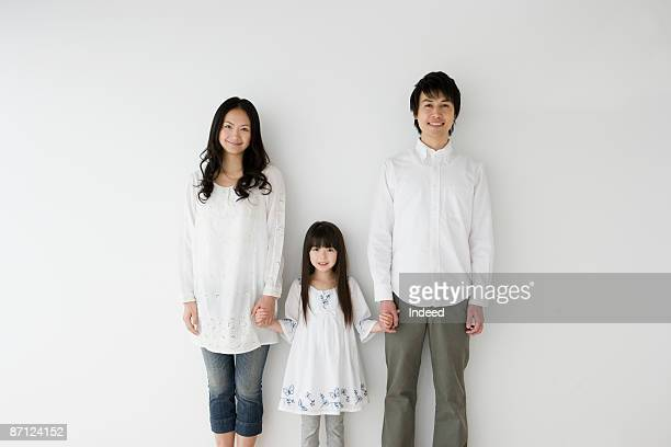Parents and daughter holding hands, portrait