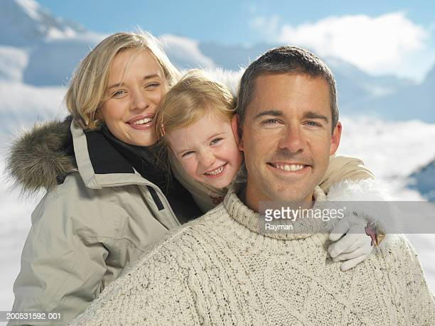 Parents and daughter (3-6) in snowscape, smiling, portrait