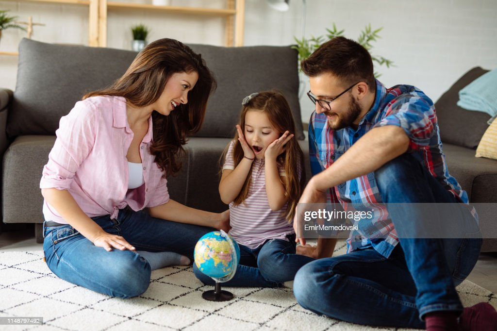 Parents and daughter looking at globe in living room : Stock Photo