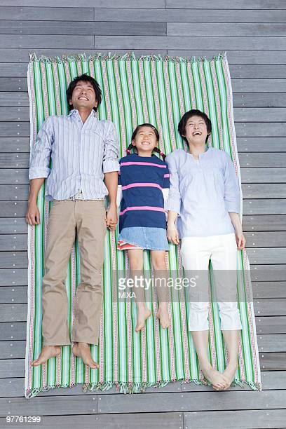 Parents and daughter lying on wood deck