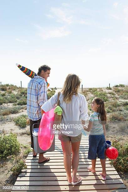 Parents and daughter (6-8) on beach path carrying picnic box and toys