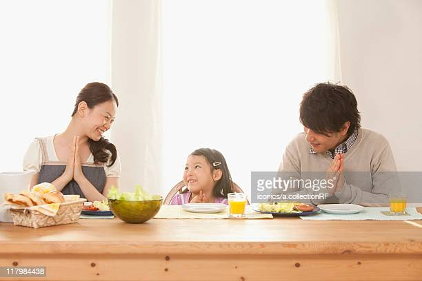 Parents and Daughter Praying at Breakfast Table