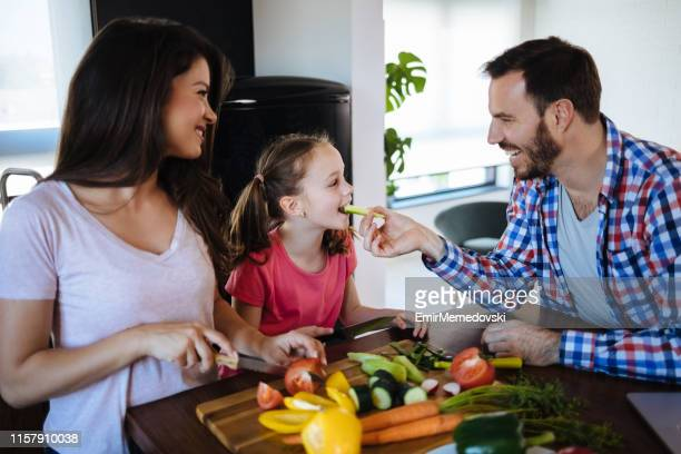 Parents and daughter preparing food together
