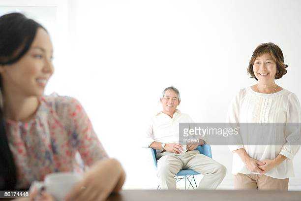 Parents and daughter relaxing in dining room