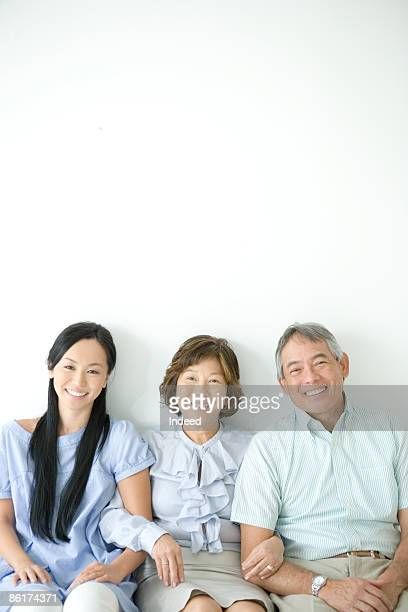 Parents and daughter sitting and smiling, portrait