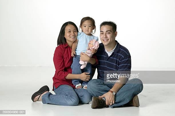 Parents and daughter (3-4) sitting, posing in studio, portrait