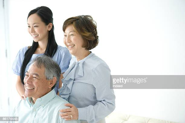 Parents and daughter smiling, looking away