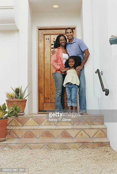parents and daughter (4-6) standing on front porch, smiling, portrait - open blouse stock photos and pictures