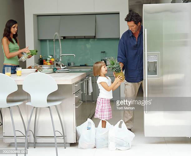 Parents and daughter (3-5) unpacking groceries in kitchen