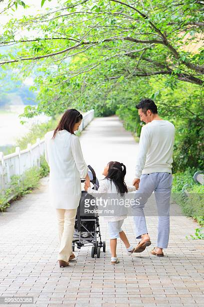 Parents and Daughter Walking in Park