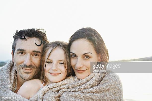 Parents and daughter wrapped in blanket