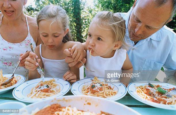 Parents and Daughters Eating Spaghetti in Garden
