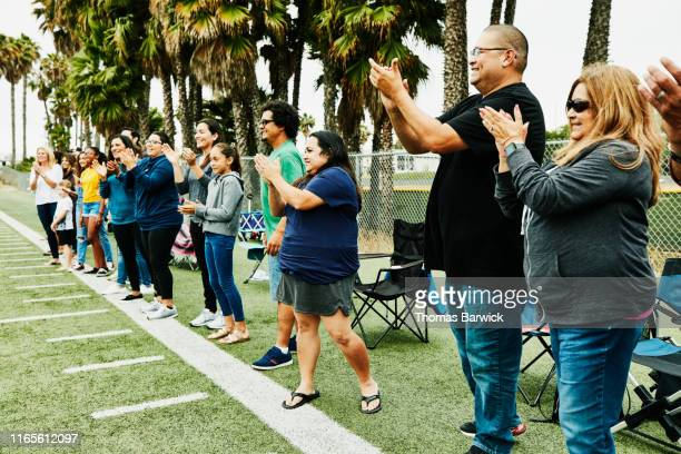 parents and families on sideline of field cheering for soccer players - sports event stock pictures, royalty-free photos & images