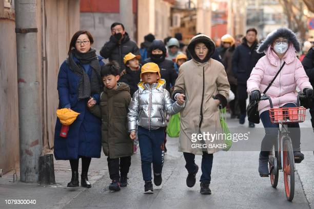 Parents and family members escort their children just outside the gates of an elementary school in Beijing following an attack on January 8 2019...