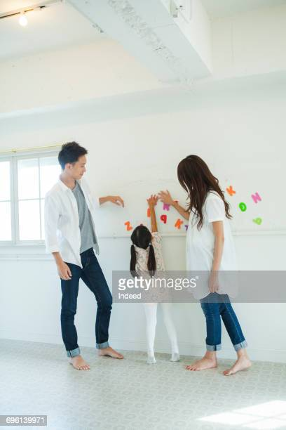 parents and girl playing with alphabet by wall - 近く ストックフォトと画像