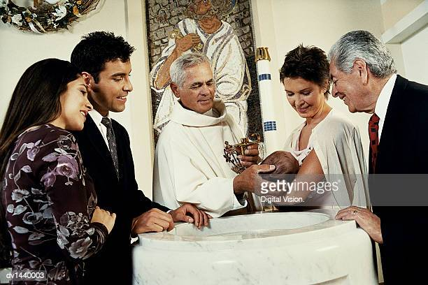 Parents and Grandparents Holding a Baby Stand Around a Baptismal Font, the Priest Baptising the Baby