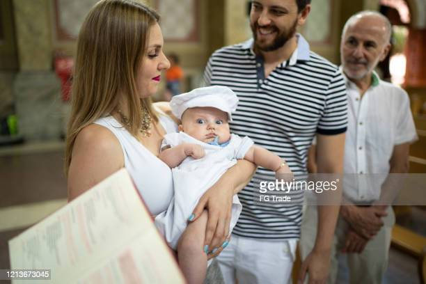 parents and his son on baptism celebration at church - catholic baptism stock pictures, royalty-free photos & images