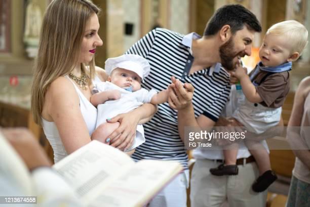 eltern und sein sohn bei tauffeier in der kirche - taufe stock-fotos und bilder