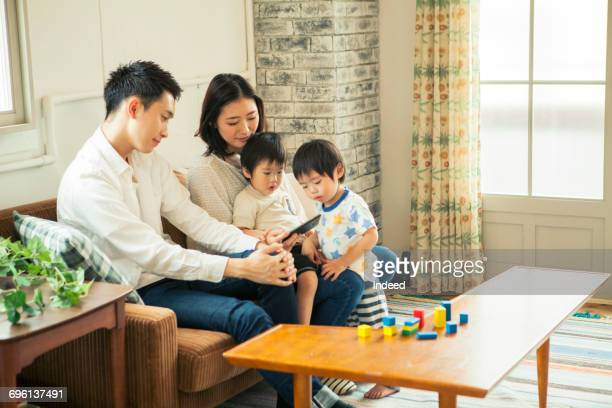 Parents and kids looking at smart phone in living room