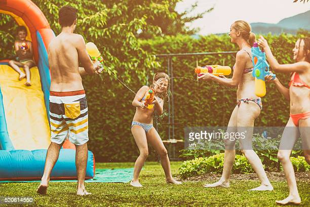 Parents and kids playing with squirt guns