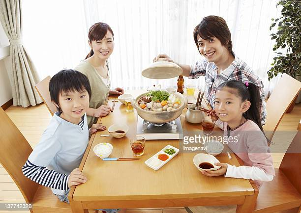 Parents and kids sitting around Japanese hot pot