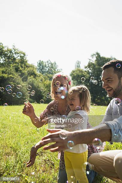 Parents and little daughter making soap bubbles on a meadow