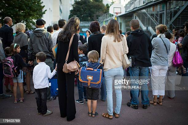 Parents and pupils wait in the courtyard of a primary school on September 3 2013 in Paris on the first day of school More than 12 million pupils went...