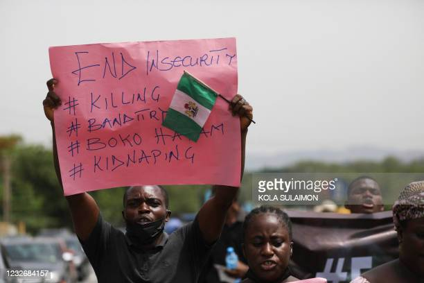 Parents and relatives of students from the Federal College of Forestry Mechanization in Kaduna who have been abducted, hold placards during a...
