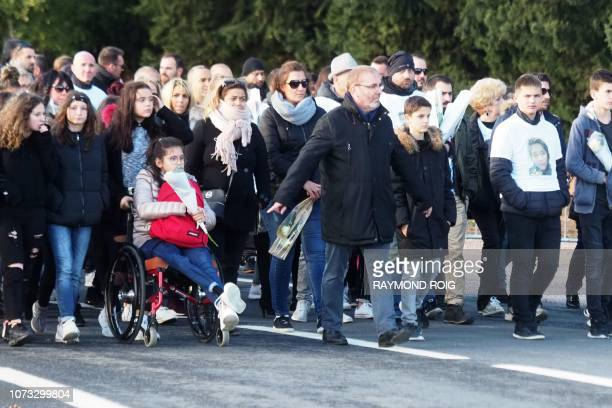Parents and relatives walk during a march held on December 14 in memory of victims dead one year before in a collision between a train and a school...