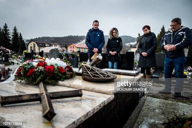 Parents and siblings of murdered journalist Jan Kuciak visit his grave at a cemetery in Stiavnik central Slovakia on December 24 2018 Jan Kuciak was...
