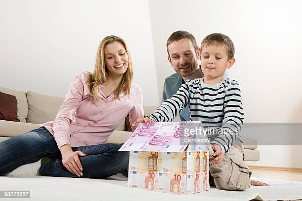 Family relaxing at home, boy (4-5) building house from Euro banknotes
