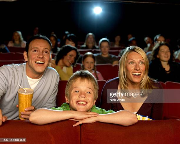 Parents and son (9-11) in cinema, laughing, close-up