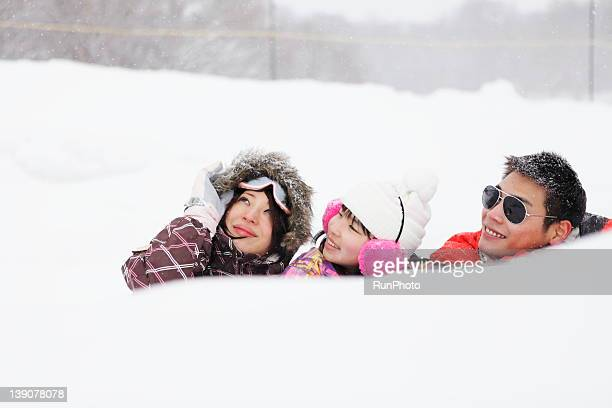 Parents and son laying in snow at ski resort