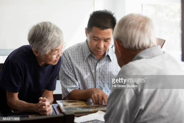 Parents and son looking at photo album