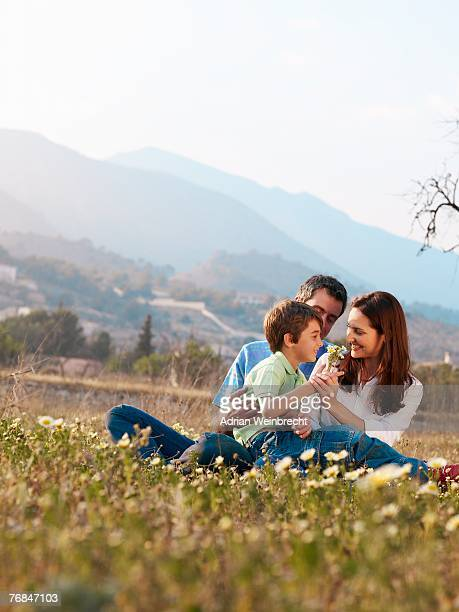 Parents and son (6-8) sitting in field, holding flowers, smiling