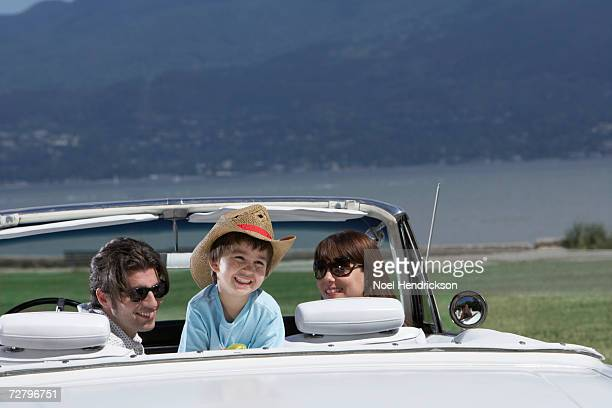 parents and son (3-4 years) sitting in white 60s convertible car, rear view - 25 29 years stock pictures, royalty-free photos & images