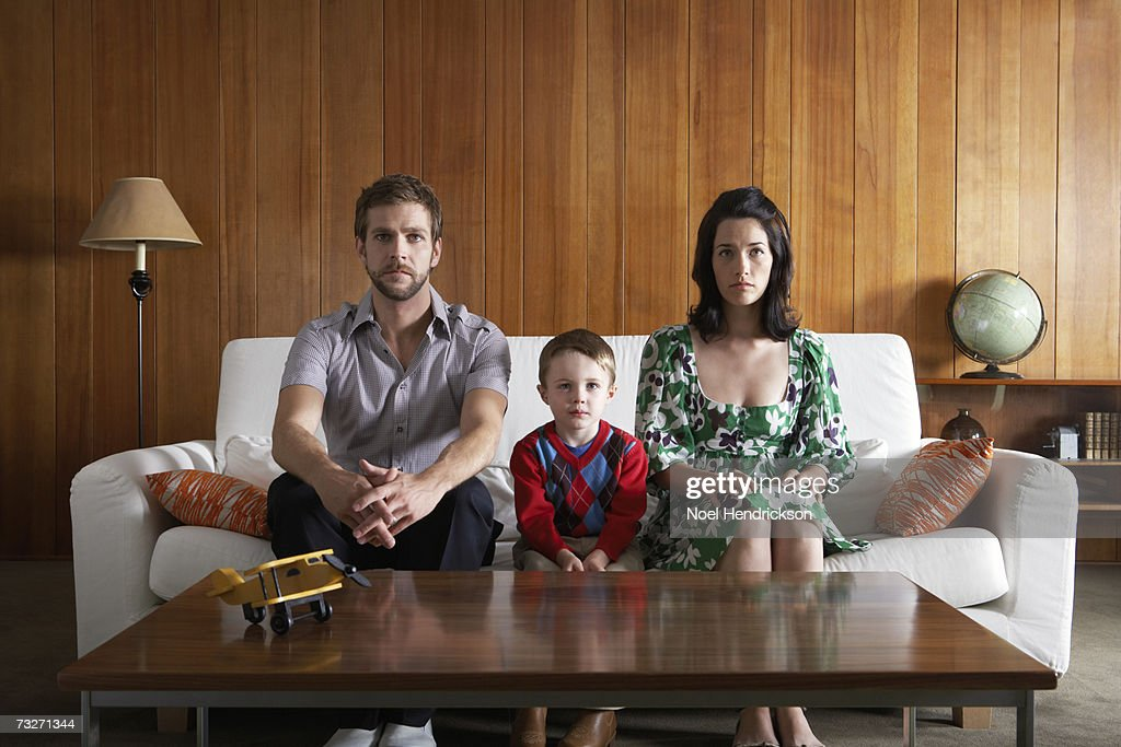 Parents and son (3-5) sitting on couch, in living room : Stock Photo