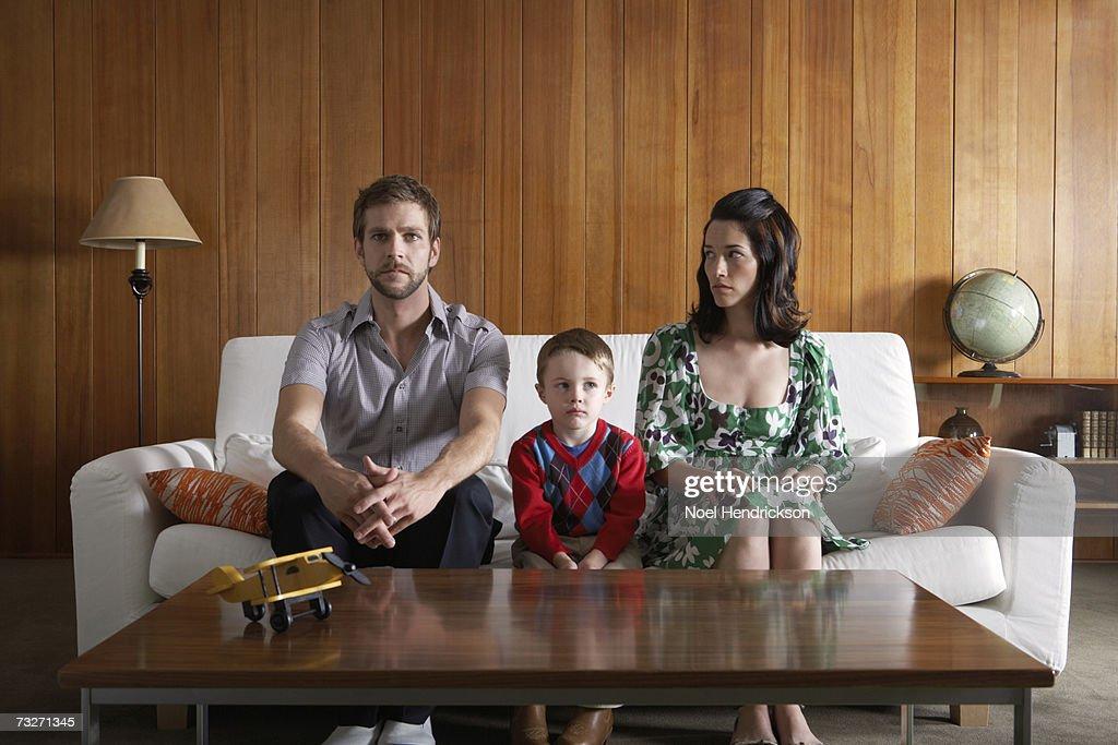 Eltern und Sohn (3-5) sitzen auf der couch im Wohnzimmer : Stock-Foto