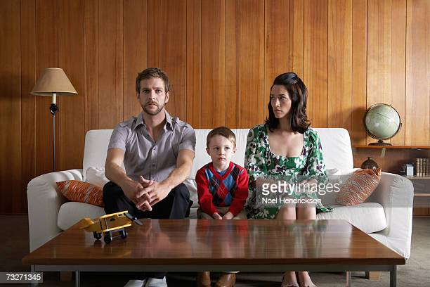 Parents and son (3-5) sitting on couch in living room