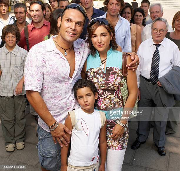 Parents and son (5-7) standing amongst crowd, smiling, portrait
