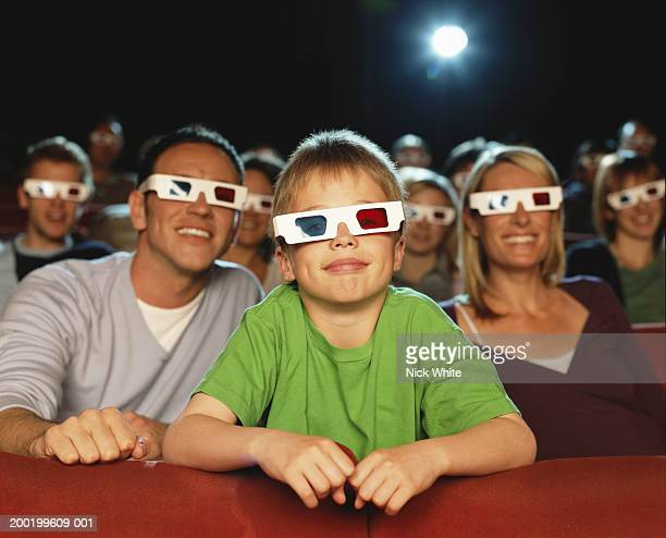 Parents and son (9-11) watching 3-D movie (focus on boy smiling)