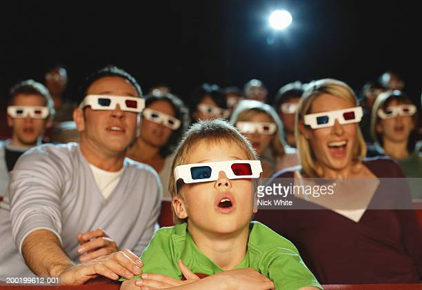 parents and son (9-11) watching 3-d movie (focus on boy reacting) - redoubtable film stock photos and pictures