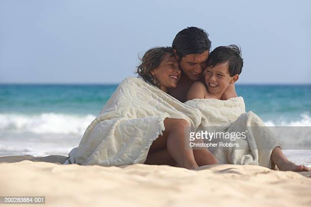 parents and son (8-10) wrapped in towel on beach, smiling - wrapped in a towel stock pictures, royalty-free photos & images
