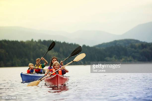 parents and sons (10-12) canoeing on lake, staffel lake, murnau, bavaria, germany - canoe stock pictures, royalty-free photos & images