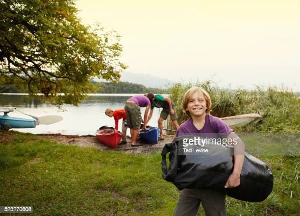 Parents and sons (10-12) unloading canoes, Staffel Lake, Murnau, Bavaria, Germany