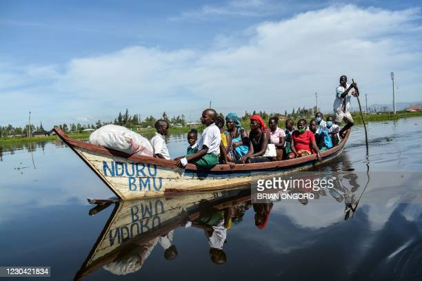 Parents and students ride on a boat to their school in a flooded water area caused by the overflow of Lake Victoria in Kisumu, Kenya, on January 4,...