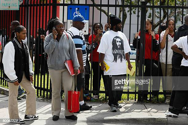 Parents and students stand near the front gate to Miami Edison Senior High School after a melee broke out in the campus courtyard February 29 2008 in...